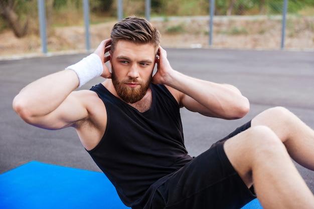 Młody brodaty sportowiec robi ćwiczenia prasowe na niebieskiej macie fitness na świeżym powietrzu