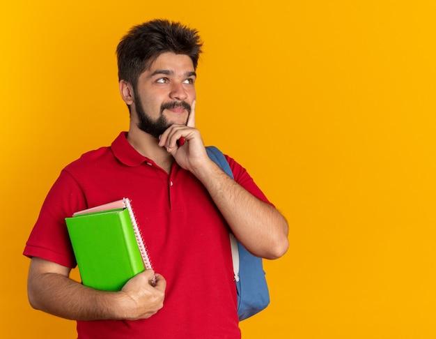 Młody brodaty student facet w czerwonej koszulce polo z plecakiem trzymającym zeszyty patrząc na bok z zamyślonym wyrazem twarzy myślący pozytywnie uśmiechnięty stojący na pomarańczowym tle