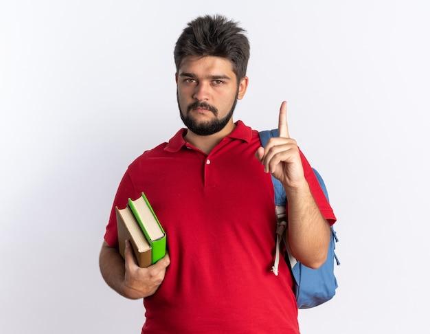 Młody brodaty student facet w czerwonej koszulce polo z plecakiem trzymającym zeszyty patrząc na kamerę z poważną twarzą pokazującą palec wskazujący stojącego na białym tle