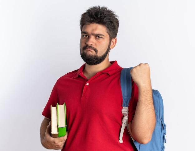 Młody brodaty student facet w czerwonej koszulce polo z plecakiem trzymającym zeszyty patrząc na kamerę z poważną twarzą zaciskającą pięść stojącą na białym tle