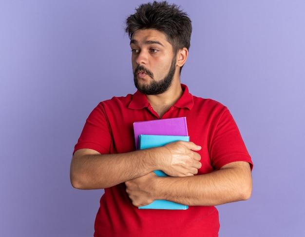 Młody, brodaty student w czerwonej koszulce polo, trzymający książki, patrzący na bok zaskoczony i zdezorientowany, stojący nad niebieską ścianą