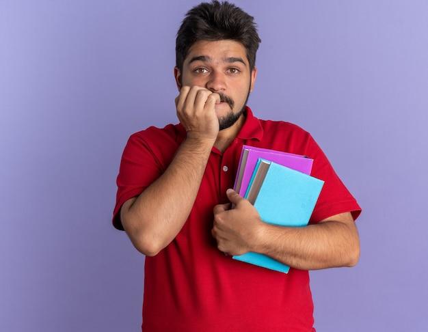 Młody brodaty student w czerwonej koszulce polo trzymający książki zestresowany i nerwowo obgryzający paznokcie stojący nad niebieską ścianą