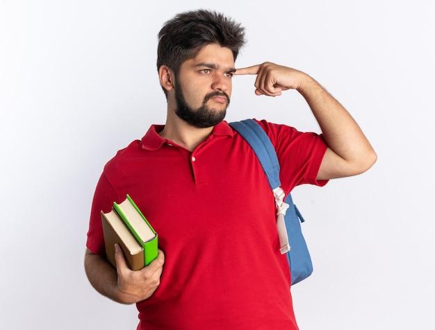 Młody, brodaty student w czerwonej koszulce polo z plecakiem, trzymający zeszyty, wskazujący palcem wskazującym na jego skroń, wyglądający pewnie myślący stojąc