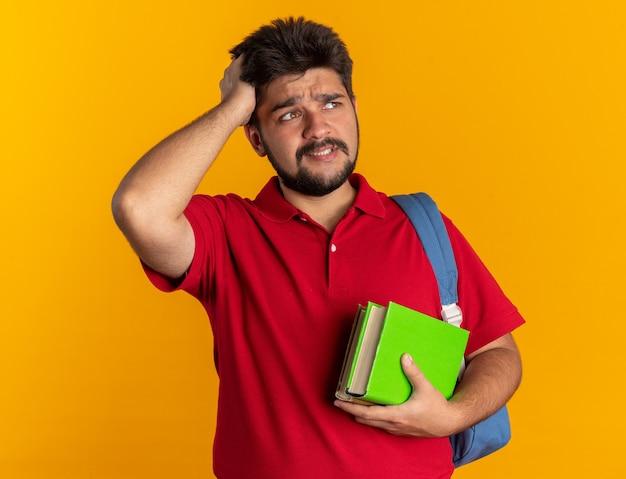 Młody, brodaty student w czerwonej koszulce polo z plecakiem trzymającym zeszyty, patrzący na bok, zmieszany z ręką na głowie za pomyłkę stojącą
