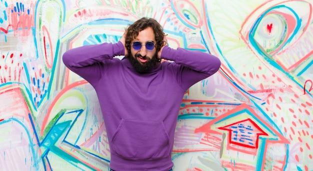 Młody brodaty szaleniec czuje się sfrustrowany i zirytowany, chory i zmęczony porażką, mający dość nudnych, nudnych zadań na ścianie graffiti