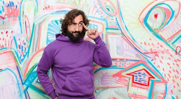 Młody brodaty szaleniec czuje się zdezorientowany lub wątpiący, koncentrując się na pomyśle, ciężko myśląc, szukając miejsca na stronie o ścianę graffiti