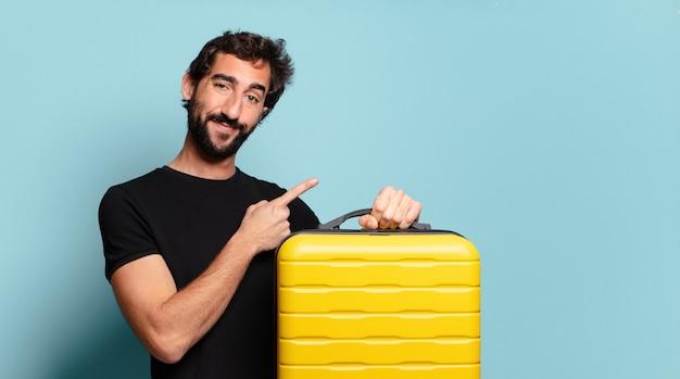 Młody brodaty szaleniec z żółtą walizką. koncepcja podróży