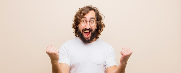 Młody brodaty szalony człowiek czuje się szczęśliwy, pozytywny i udany, świętując zwycięstwo, osiągnięcia lub powodzenia przeciwko płaskiemu kolorowi