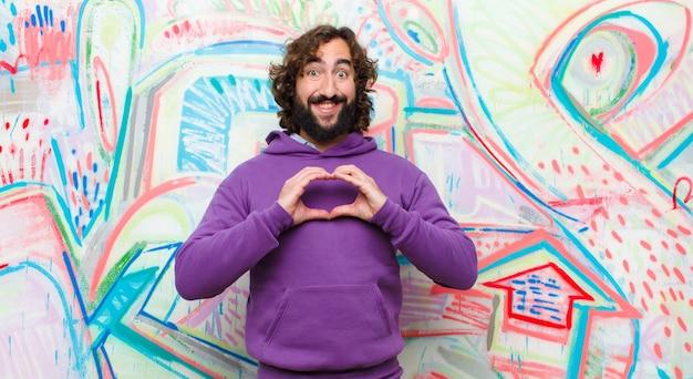 Młody brodaty szalony człowiek uśmiecha się i czuje się szczęśliwy, słodki, romantyczny i zakochany, tworząc kształt serca obiema rękami na ścianie graffiti
