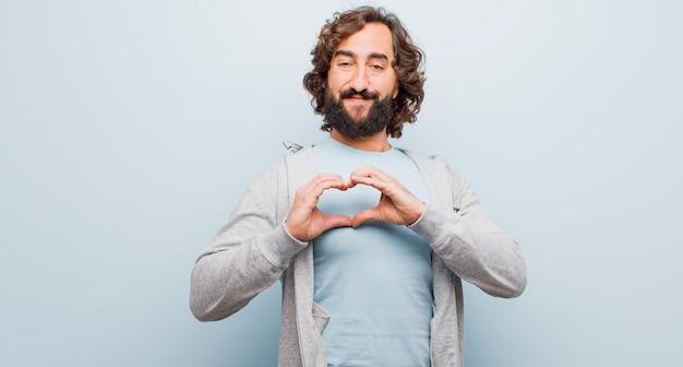 Młody brodaty szalony człowiek uśmiecha się i czuje się szczęśliwy, uroczy, romantyczny i zakochany, dzięki czemu obie ręce mają kształt serca