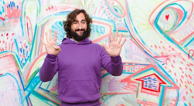 Młody brodaty szalony człowiek uśmiecha się i wygląda przyjaźnie, pokazuje numer dziewięć lub dziewiąty ręką do przodu, odliczając do ściany graffiti