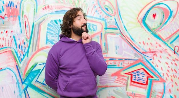 Młody brodaty szalony człowiek uśmiecha się radośnie i marzy lub wątpi, patrząc z boku na ścianę graffiti