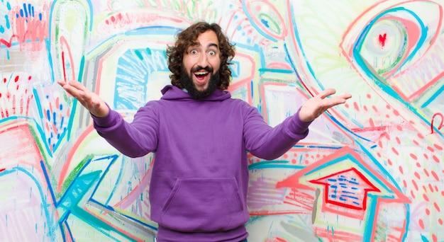 Młody brodaty szalony człowiek uśmiecha się wesoło, dając ciepłe, przyjazne, kochające powitanie, czując się szczęśliwy i uroczy na ścianie graffiti