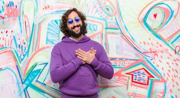 Młody brodaty szalony czuje się romantyczny, szczęśliwy i zakochany, uśmiecha się wesoło i trzyma ręce blisko serca przy ścianie graffiti