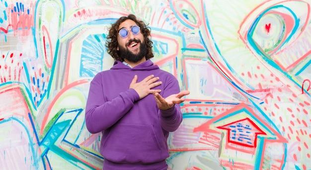 Młody brodaty szalony czuje się szczęśliwy i zakochany, uśmiechając się jedną ręką obok serca, a drugą wyciągnął przed graffiti