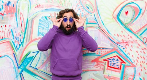 Młody brodaty szalony czuje się zszokowany, zdziwiony i zaskoczony, trzyma okulary ze zdziwionym, niedowierzającym spojrzeniem na graffiti