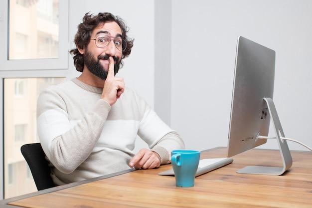 Młody brodaty szalony freelancer pracuje z jego komputerem