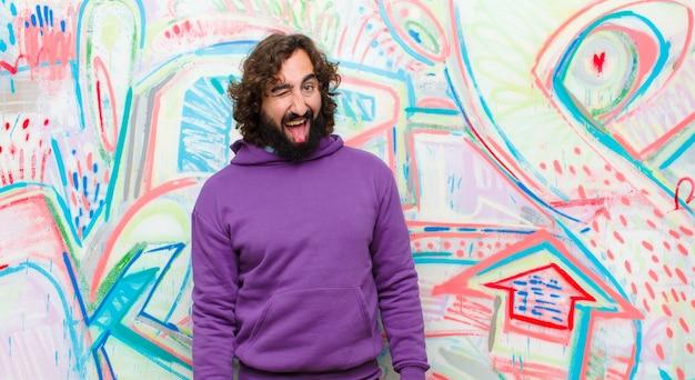 Młody, brodaty szalony mężczyzna o pogodnym, beztroskim, buntowniczym nastawieniu, żartujący i wystający język, dobrze bawiący się przed graffiti