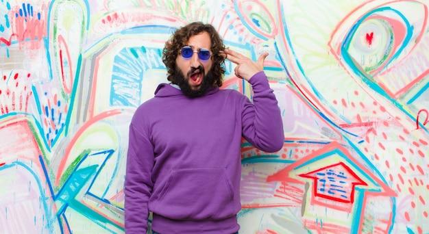Młody brodaty szalony mężczyzna patrząc niezadowolony i zestresowany, gest samobójczy czyniąc znak pistoletu ręką, wskazując głową na ścianie graffiti