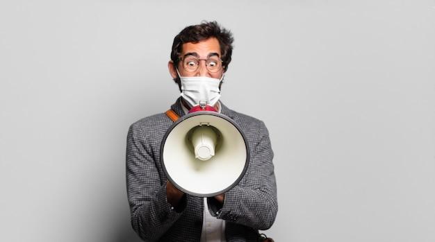 Młody brodaty szalony mężczyzna protestujący z megafonem