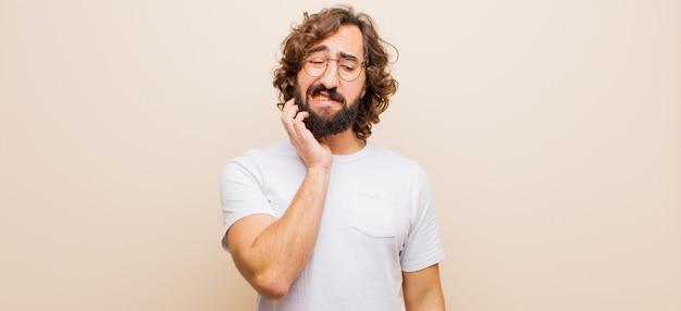 Młody brodaty szalony mężczyzna trzyma policzek i cierpi bolesny ból zęba, czuje się chory, nieszczęśliwy i niezadowolony, szuka dentysty na płaski kolor