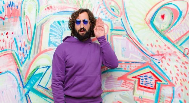 Młody brodaty szalony mężczyzna wygląda poważnie i ciekawie, słucha, próbuje usłyszeć tajną rozmowę lub plotkę, podsłuchuje ścianę graffiti