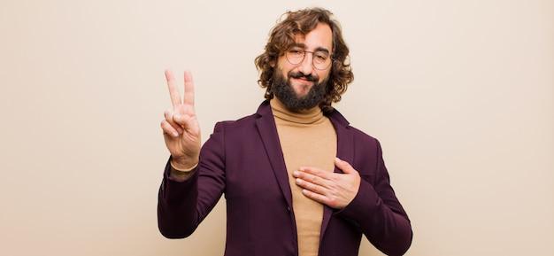 Młody brodaty szalony mężczyzna wygląda szczęśliwy, pewny siebie i godny zaufania, uśmiecha się i pokazuje znak zwycięstwa, z pozytywnym nastawieniem do różowej ściany