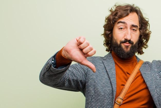 Młody brodaty szalony mężczyzna wyglądający na smutnego, rozczarowanego lub wściekłego, pokazujący kciuki w nieporozumieniu, czujący się sfrustrowany