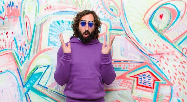 Młody brodaty szalony mężczyzna wyglądający na zszokowanego i zdziwionego, ze szczęką opadającą ze zdziwienia na widok czegoś niewiarygodnego na tle graffiti