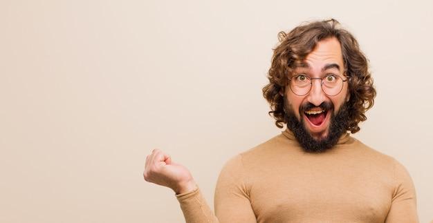 Młody brodaty szalony mężczyzna wyglądający niezwykle szczęśliwy i zaskoczony, świętujący sukces, krzyczący i skaczący