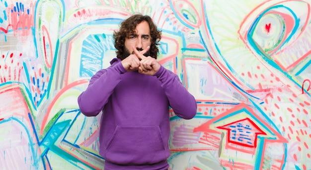 Młody brodaty szalony mężczyzna wyglądający poważnie i niezadowolony z odrzuconymi palcami z przodu, proszący o ciszę na ścianie graffiti