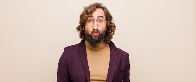 Młody brodaty szalony mężczyzna zaciskający usta wraz z uroczym, zabawnym, szczęśliwym, uroczym wyrazem twarzy, wysyłający buziaka przeciwko płaskiemu kolorowi