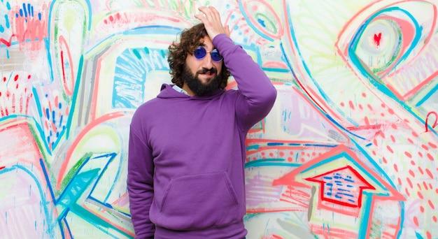 Młody brodaty szalony panikuje nad zapomnianym terminem, czuje się zestresowany, musi ukryć bałagan lub pomyłkę na ścianie graffiti