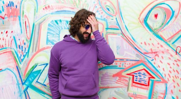 Młody brodaty szalony śmiech i uderzanie się w czoło, jak mówienie o! zapomniałem lub to był głupi błąd na ścianie graffiti
