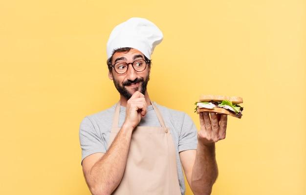 Młody brodaty szef kuchni myśli wyrażenie i trzyma kanapkę