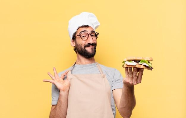 Młody brodaty szef kuchni szczęśliwy wyraz twarzy i trzymający kanapkę