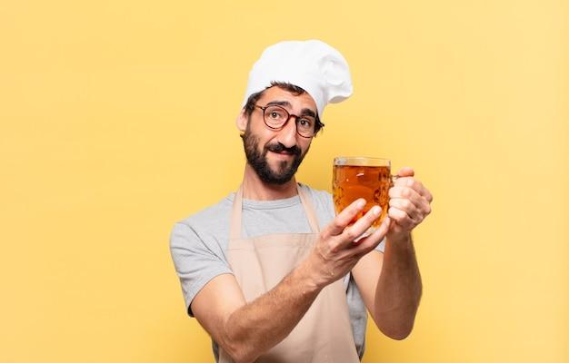 Młody brodaty szef kuchni szczęśliwy wyraz twarzy i trzymający piwo