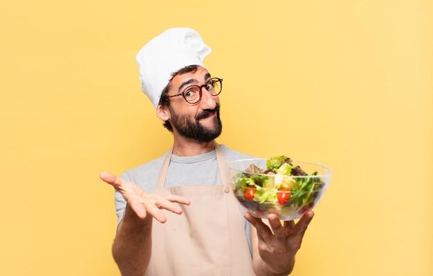Młody brodaty szef kuchni szczęśliwy wyraz twarzy i trzymający sałatkę