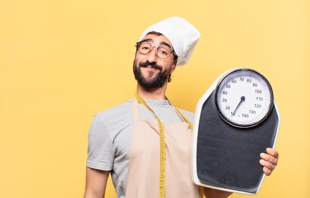 Młody brodaty szef kuchni szczęśliwy wyraz twarzy i trzymający wagę