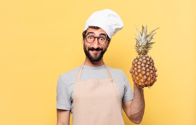 Młody brodaty szef kuchni szczęśliwy wyraz twarzy trzymający ananasa