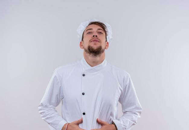 Młody brodaty szef kuchni w białym mundurze, trzymając rękę na brzuchu, patrząc na białej ścianie