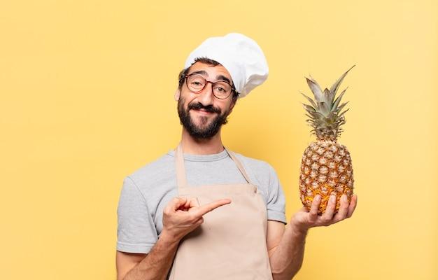 Młody brodaty szef kuchni wskazujący lub pokazujący trzyma ananasa