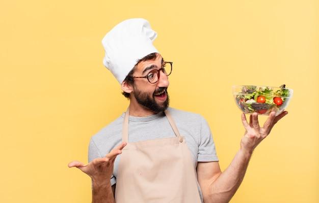 Młody brodaty szef kuchni zaskoczony wyrazem twarzy i trzymający sałatkę