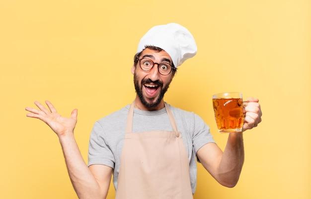 Młody brodaty szef kuchni zaskoczony wyrazem twarzy i trzymającym piwo
