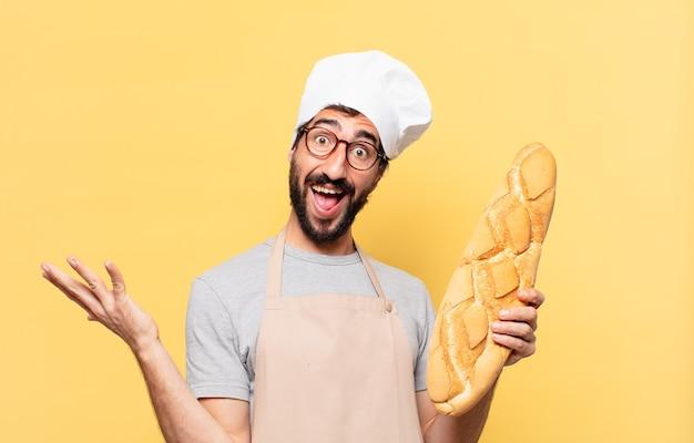 Młody brodaty szef kuchni zaskoczony wyrazem twarzy trzymającym chleb