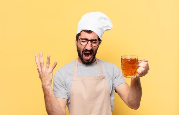 Młody brodaty szef kuchni zły wyraz twarzy i trzymający piwo