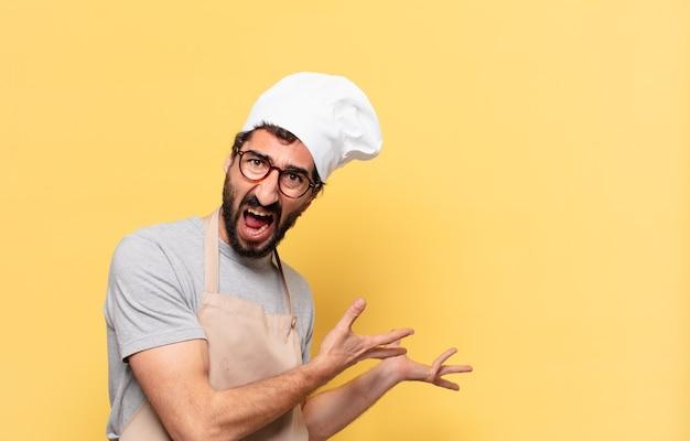 Młody brodaty szef kuchni zły wyraz twarzy