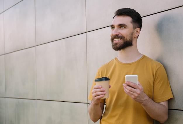 Młody brodaty trzymając smartfon i filiżankę kawy