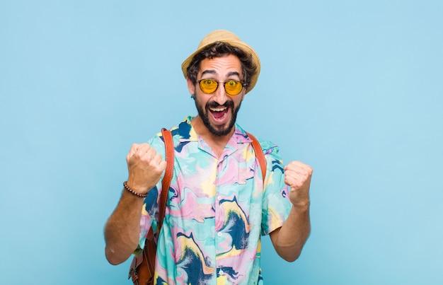 Młody, brodaty turysta czuje się szczęśliwy, pozytywnie i pomyślnie, świętuje zwycięstwo, osiągnięcia lub powodzenia