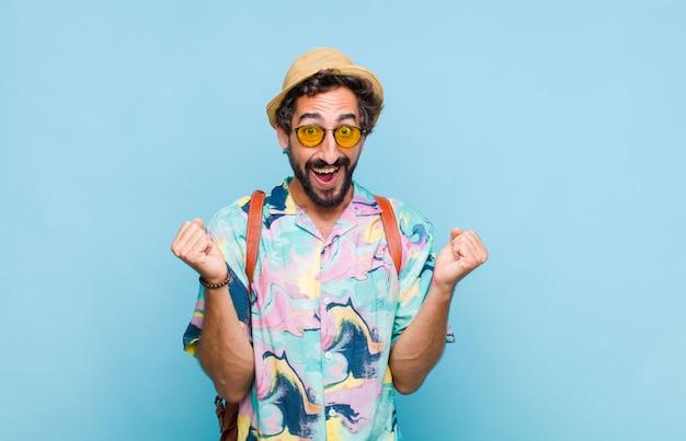 Młody brodaty turysta czuje się zszokowany, podekscytowany i szczęśliwy, śmieje się i świętuje sukces, mówiąc wow!